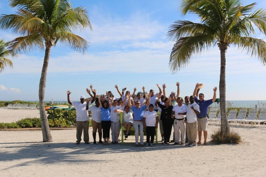 the Island Inn team in big chair on beach